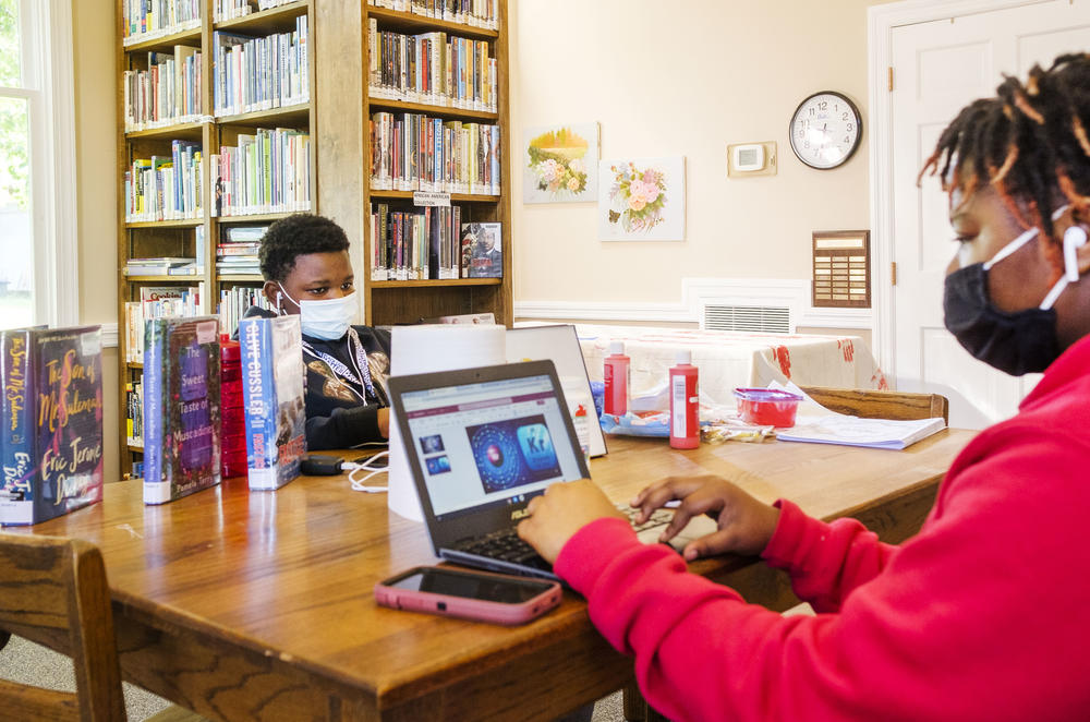 """Siblings Quinyonna Tooks, right, and Charles Knott do their schoolwork in the Oglethorpe Library in Macon County. Charles is not a fan of remote learning. """"I don't like it,"""" he said. """"In school is better for me. I can focus in there with the teachers."""""""