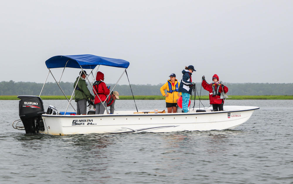 a small group of people in rain gear on a skiff