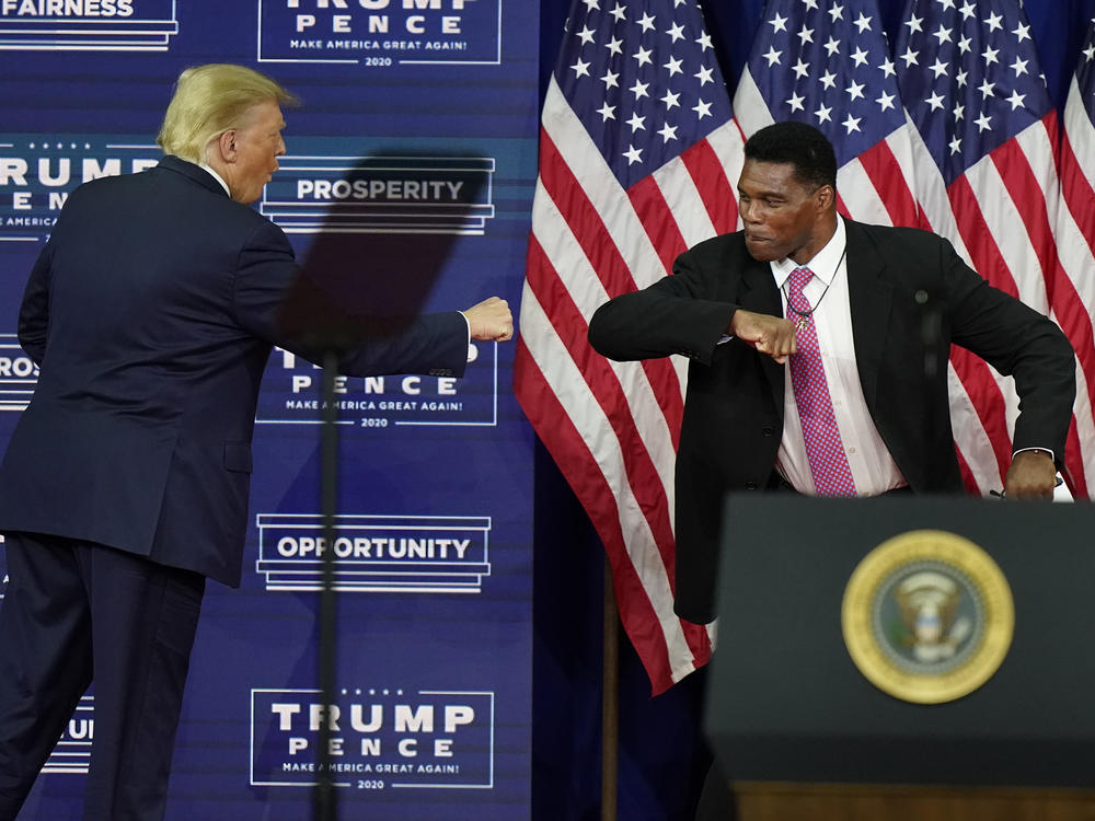 Then-President Donald Trump elbow bumps Herschel Walker during a 2020 campaign rally in Atlanta. Walker filed paperwork Tuesday to run for U.S. Senate in the key swing state of Georgia.