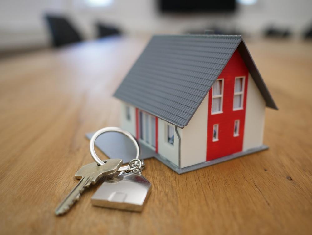 A photo of a house key next to a miniature house