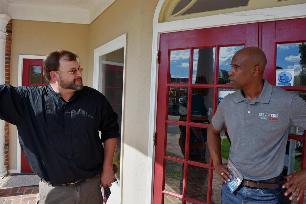 Professional blacksmith Trenton Tye (left) speaks with U.S. Senate candidate Kelvin King about revitalizing rural Georgia.