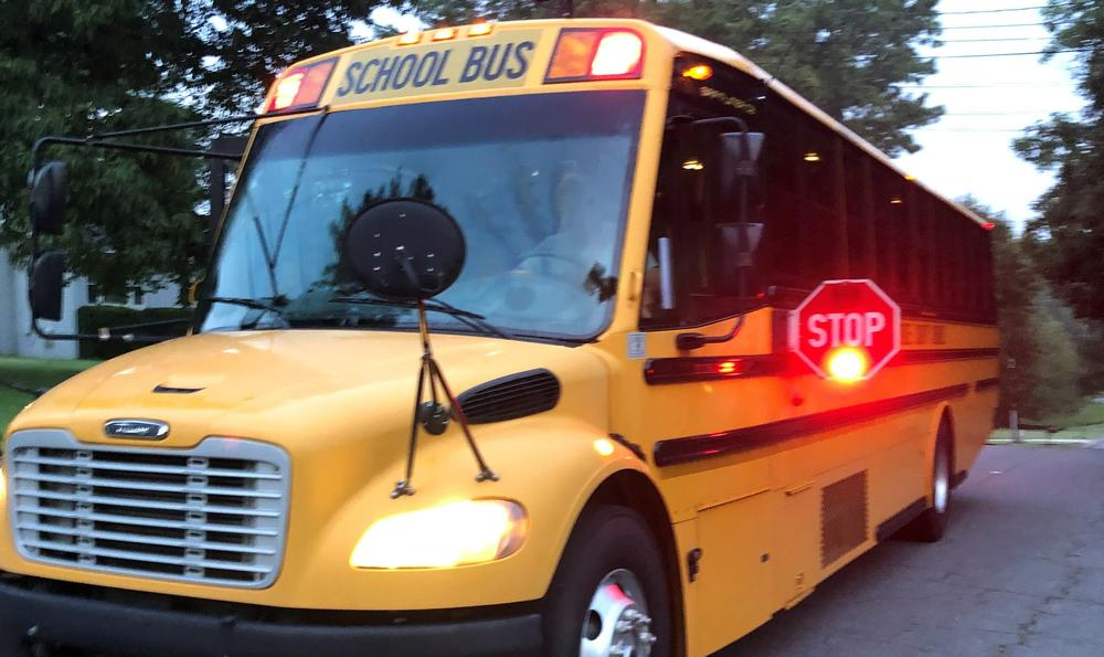 A school bus with its stop sign closing