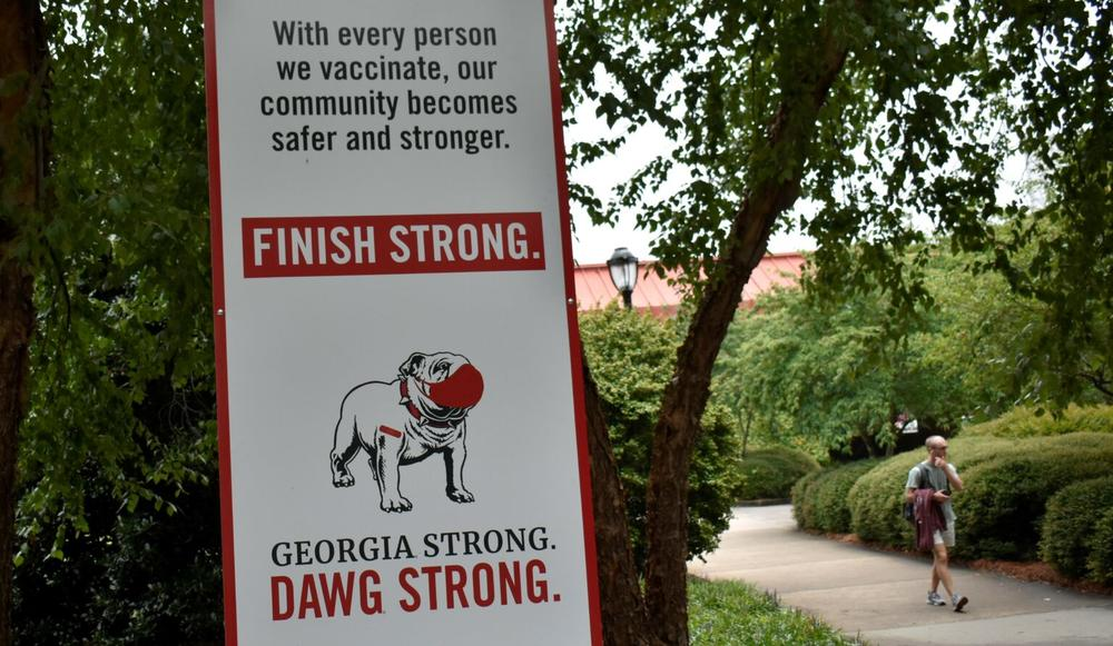 A sign at the University of Georgia encourages students to vaccinate and mask up. Some professors want face coverings to be required.