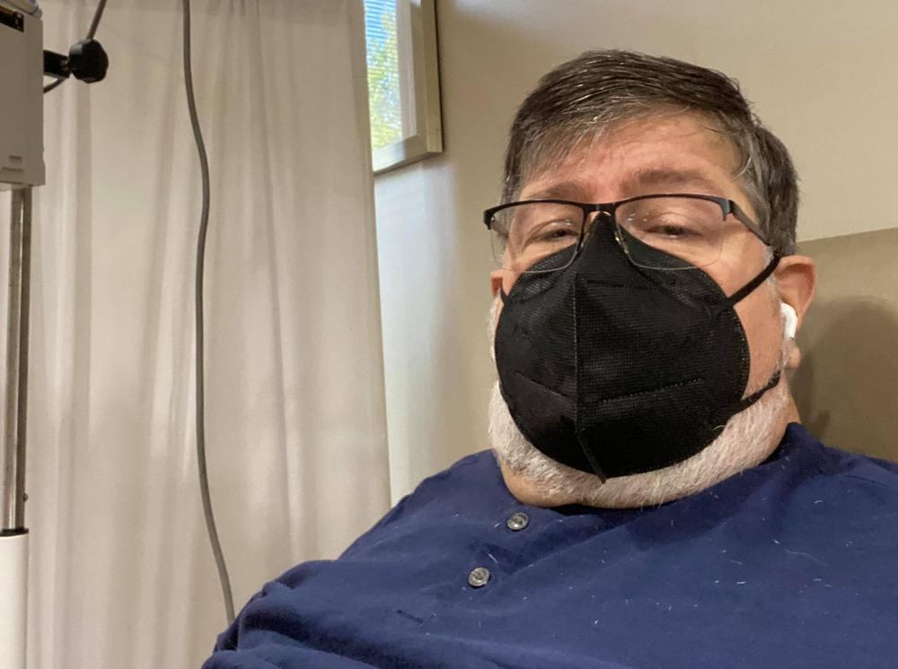 Dennis Loubiere in a black face mask while receiving an infusion of monoclonal antibodies