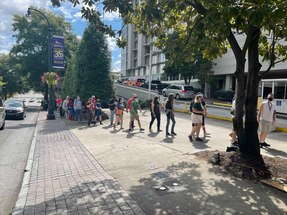 Attendees wait in line Thursday for admission to Dragon Con 2021.