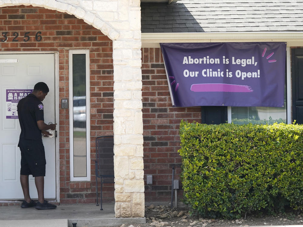 A security guard opens the door to the Whole Women's Health Clinic in Fort Worth, Texas, Wednesday, on Sept. 1, 2021.