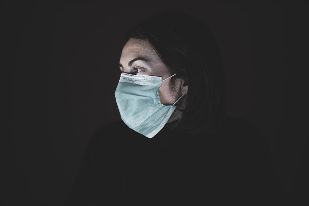 A person in a surgical mask looking to the right