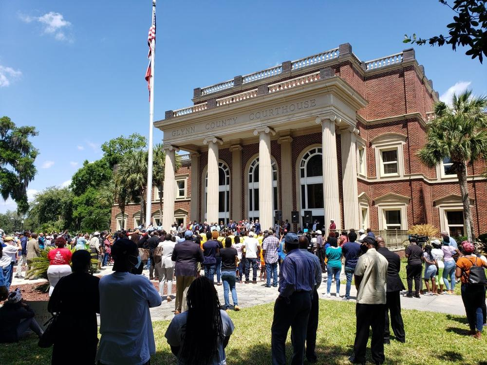 Crowds are set to gather outside the Glynn County courthouse starting Monday when jury selection for the Ahmaud Arbery murder trial begins. The media spotlight is about to train intensely on the small coastal Georgia town. In this May 2020 photo, crowds gathered on the lawn as a grand jury considered murder indictments.