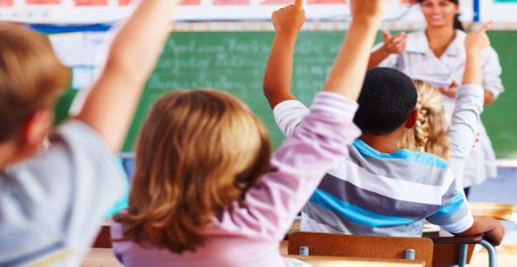 Children raising their hands in a classroom.