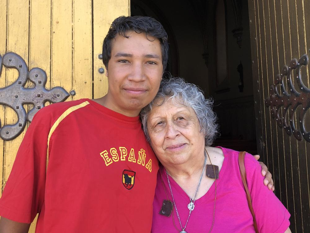 Matthias Bowie and his grandmother Lynda Martinez stand outside the Shrine of Our Lady of Lourdes after a recent morning mass in Ohkay Owingeh Pueblo.