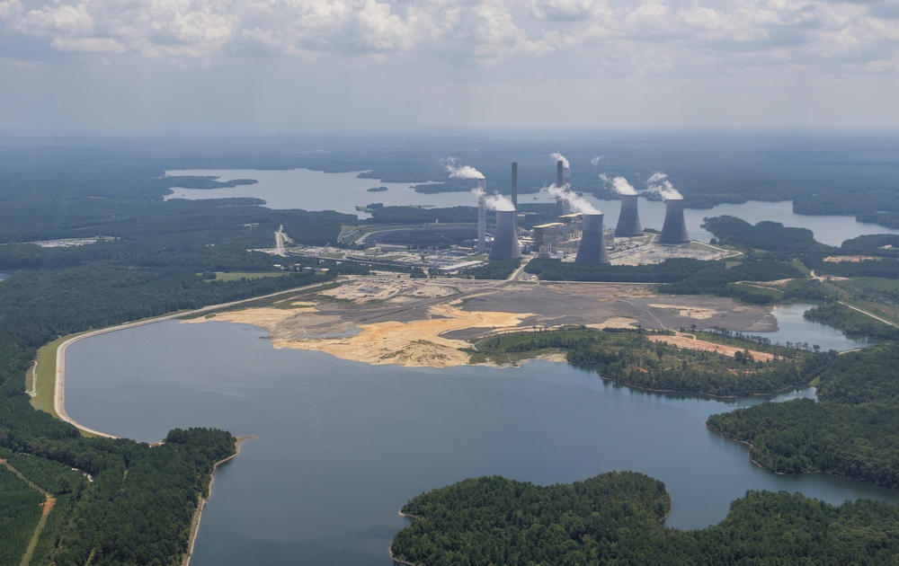 The coal ash pond, foreground, where waste from Georgia Power's coal fired Plant Scherer is stored, in August of 2019. The coal ash is partially submerged in the local aquifer.