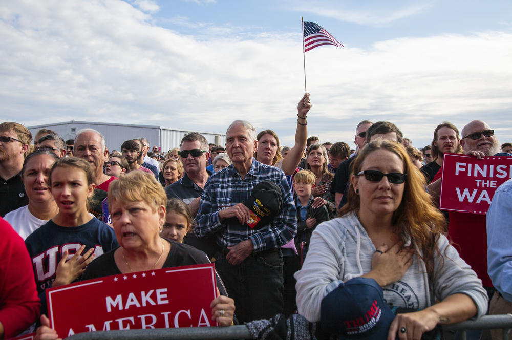 People gathered to hear President Trump campaign fo Georgia Republican gubernatorial candidate Brian Kemp pause for the National Anthem Sunday in Macon, Ga.