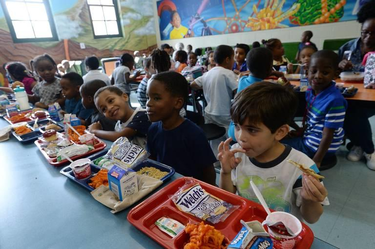 Kindergartner Landon Hall (right) licks his fingers as he finishes off his peanut butter and jelly sandwich at Alexander II Magnet School where students began their lunch at 10:30 in the morning.