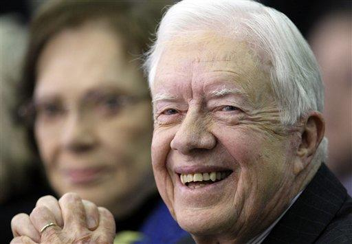 Former U.S. President Jimmy Carter smiles as his wife Rosalynn, rear, in March 2010.