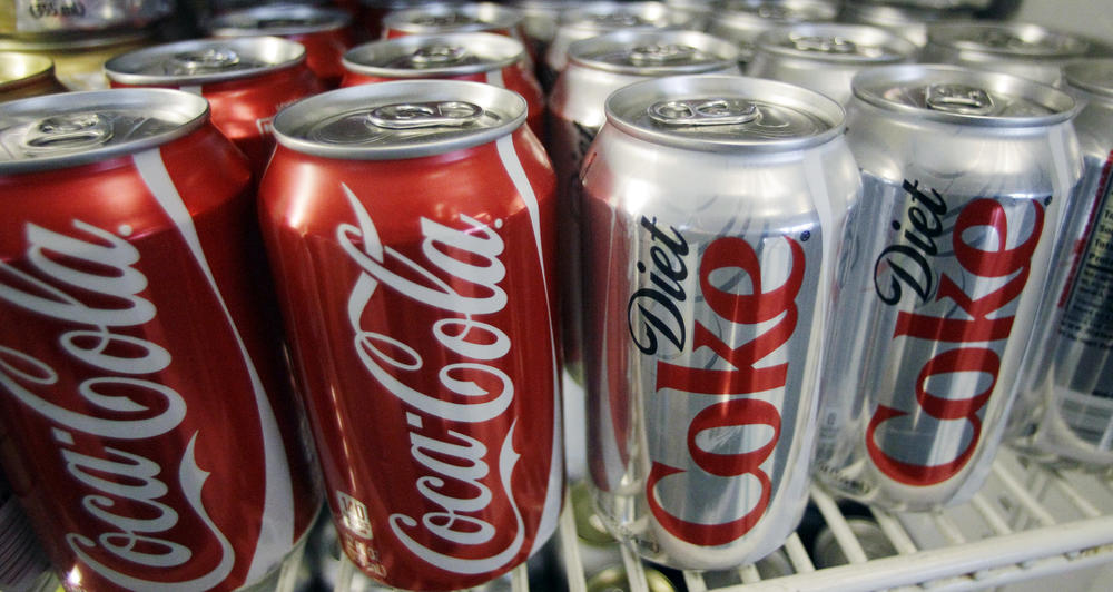 In this March 17, 2011, file photo, cans of Coca-Cola and Diet Coke sit in a cooler in Anne's Deli in Portland, Ore. The Coca-Cola Co. plans to help collect and recycle a bottle or can for every one that it sells by 2030.