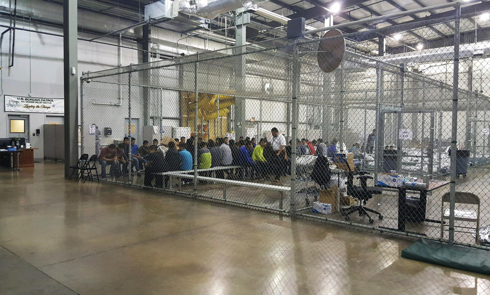 In this photo provided by U.S.People who've been taken into custody related to cases of illegal entry into the United States sit in one of the cages at a facility in McAllen, Texas, Sunday, June 17, 2018.