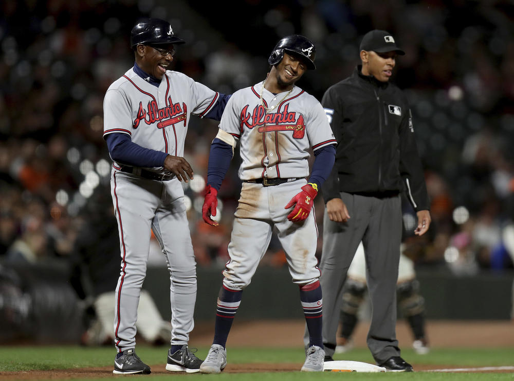 Atlanta Braves shortstop Ozzie Albies (1) and Atlanta Braves third base coach Ron Washington (37) smile after Albies doubled and advanced to third on a throwing error by Gorkys Hernández in the seventh inning of a baseball game in San Francisco.