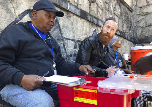 Harry Ethridge, client services manager at the Atlanta Harm Reduction Coalition, and Jonathan Spuhler, an outreach coordinator for Absolute Care and volunteer at AHRC, set up a needle exchange station for drug users to swap used syringes for clean ones..