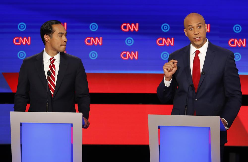 Former Housing and Urban Development Secretary Julian Castro listens as Sen. Cory Booker, D-N.J., speaks during the second of two Democratic presidential primary debates hosted by CNN Wednesday, July 31, 2019, in the Fox Theatre in Detroit.