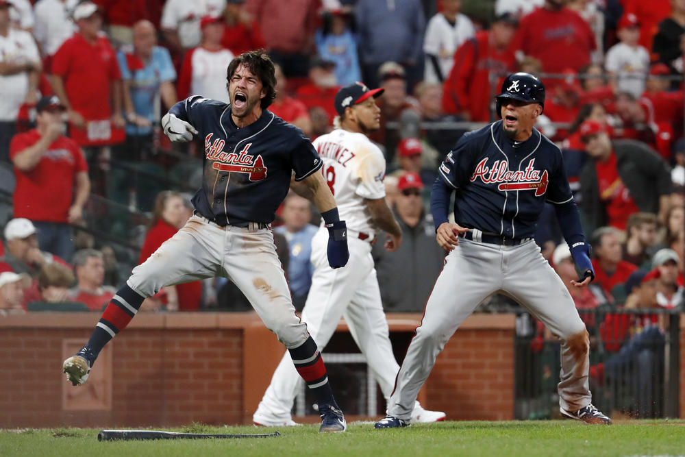 Atlanta Braves' Dansby Swanson, left, and Rafael Ortega, right, celebrate after scoring as St. Louis Cardinals relief pitcher Carlos Martinez (18) walks in the background during the ninth inning in Game 3 of a baseball National League Division Series.