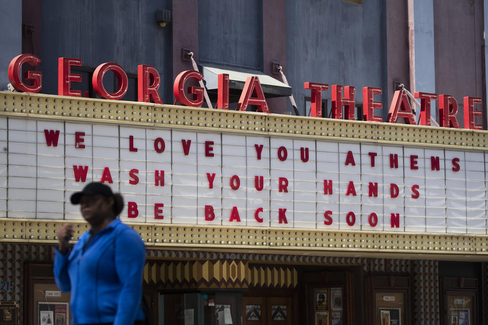 A woman walks past the Georgia Theatre Friday, March 20, 2020, in downton Athens, Ga. A note posted on the theatre's door says they are closed and all shows are postponed.