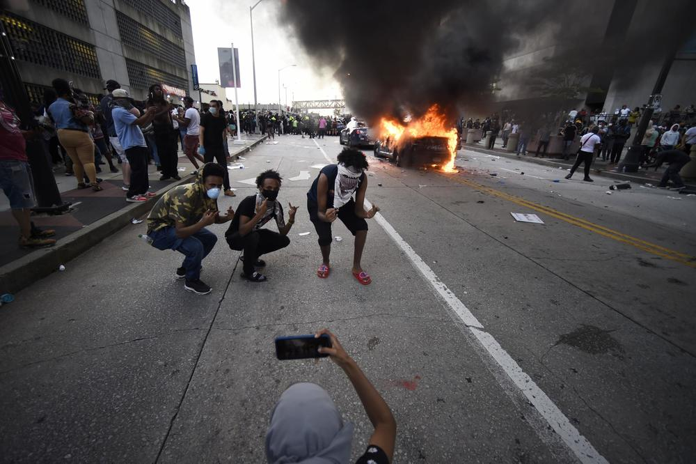 An Atlanta Police Department vehicle burns as people pose for a photo during a demonstration against police violence, Friday, May 29, 2020 in Atlanta. The protest started peacefully earlier in the day before demonstrators clashed with police.