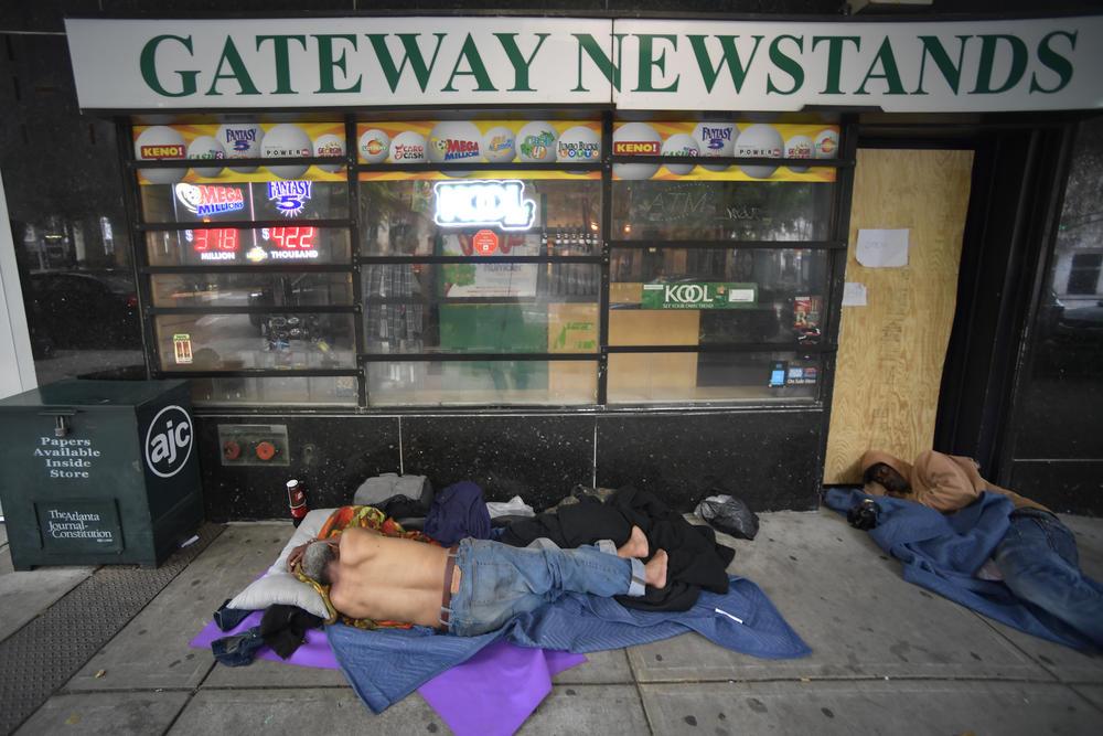 Homeless men sleep on Marietta Street Friday, June 5, 2020, in Atlanta.