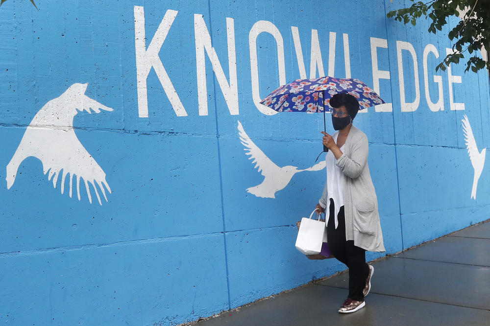 A woman wearing a mask due to coronavirus concerns walks by a public library, Tuesday, June 30, 2020, in Cambridge, Mass.