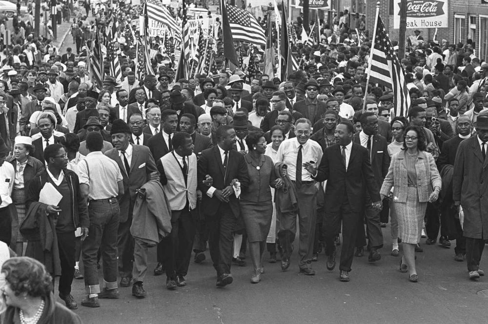 Dr. Martin Luther King Jr. and fellow civil rights activists march across the Alabama River on the first of a five-day, 50-mile march to the state capitol at Montgomery, Alabama, on March 21, 1965.