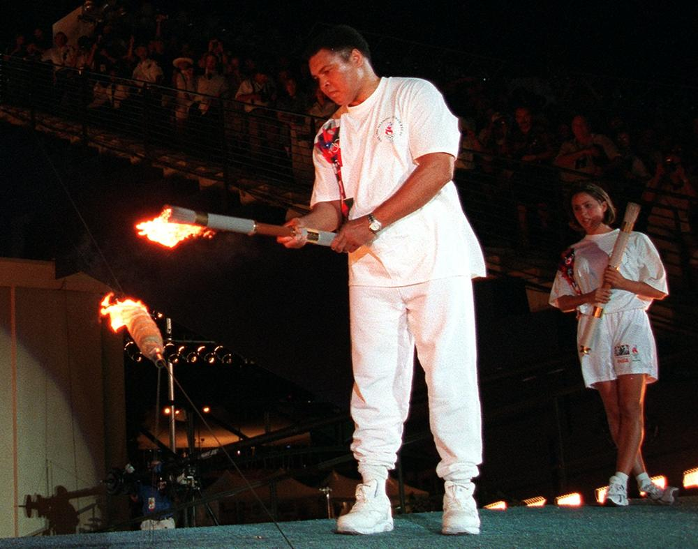 American swimmer Janet Evans looks on as Muhammad Ali lights the Olympic flame during the 1996 Summer Olympic Games opening ceremony in Atlanta Friday, July 19, 1996.