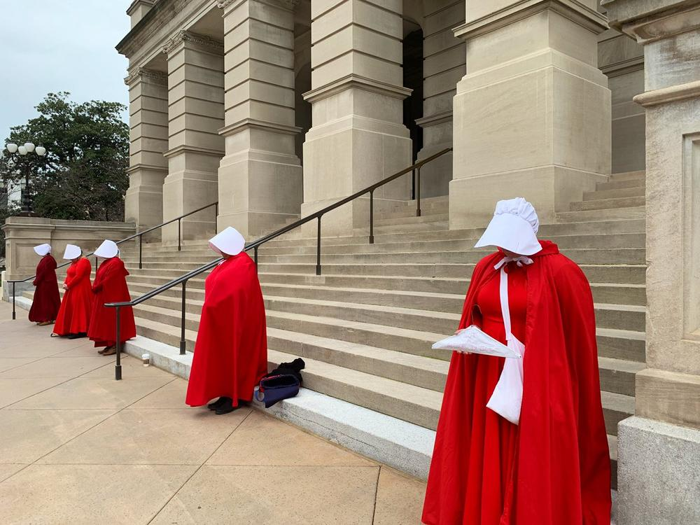 Women dressed in 'Handmaid's Tale' costumes stand outside the Georgia State Capitol in protest to 'Heartbeat Bill.'