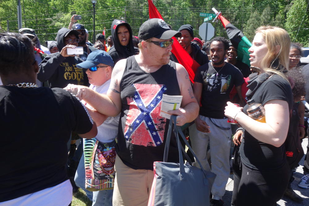 Black Lives Matter protestors confront a pair of Confederate supporters.