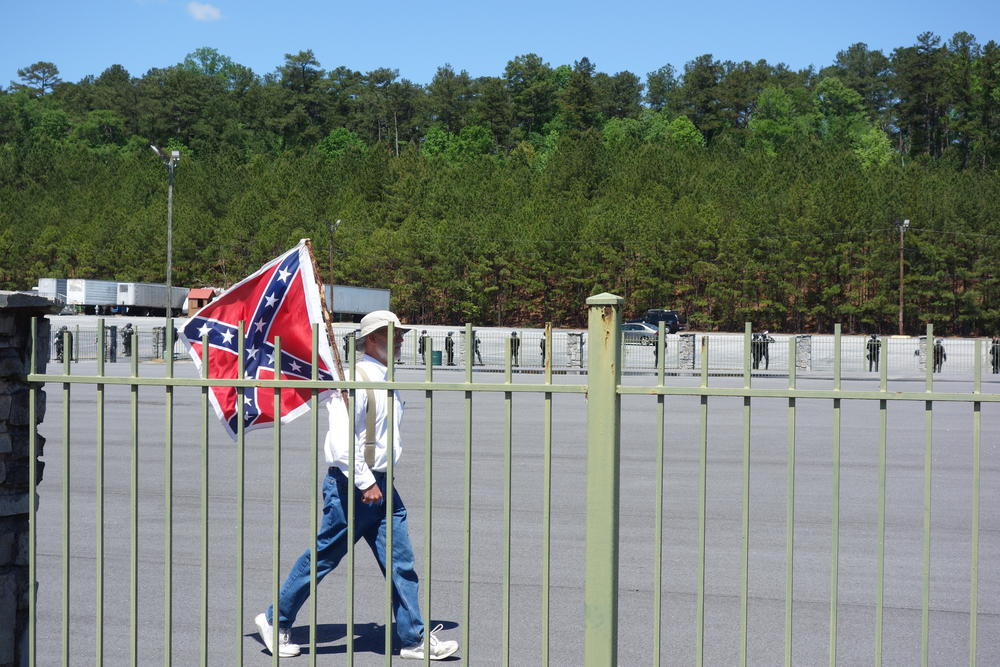 A man holds a Confederate flag as he paces the fenced demonstration area.