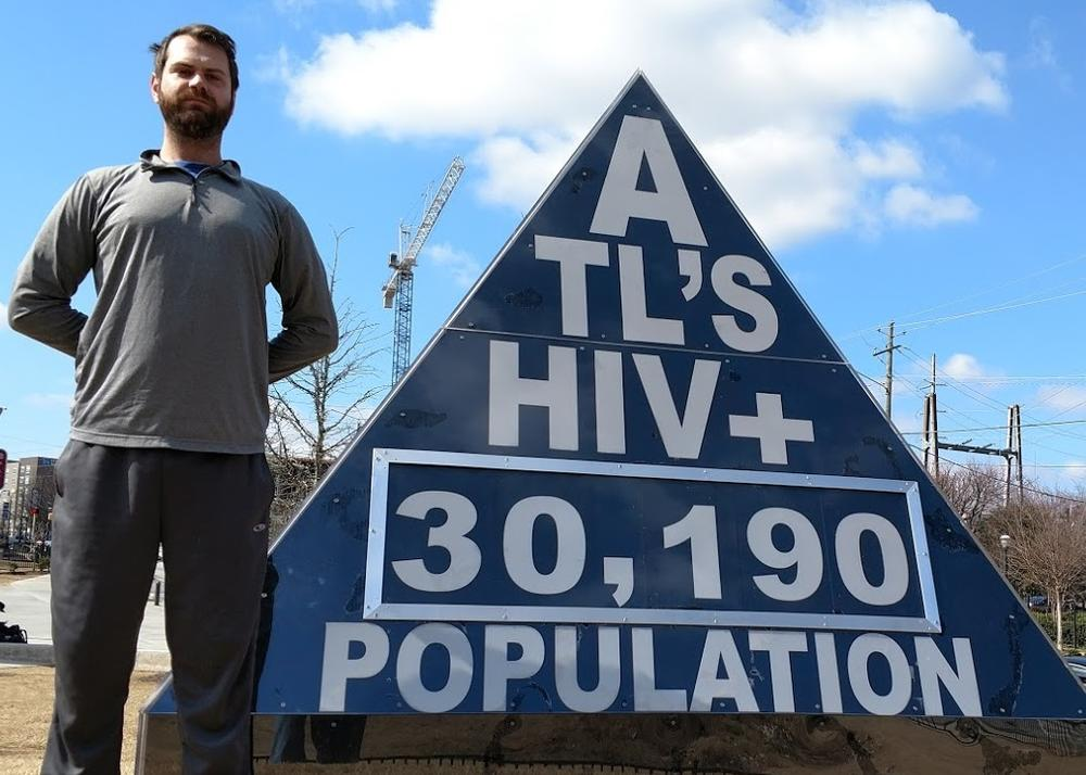In this Feb. 19, 2017  photo, freelance journalist Matt Terrell stands next to a marker he designed that shows Atlanta's HIV infection rate, which is updated once a week. It is on display outside the Center for Civil and Human Rights in Atlanta.