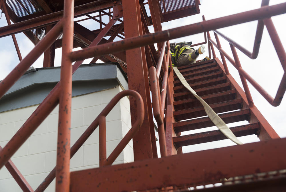 One of the Dodge State Prison firefighters scrambles up a disused guard tower they now use for training during a training demonstration recently.