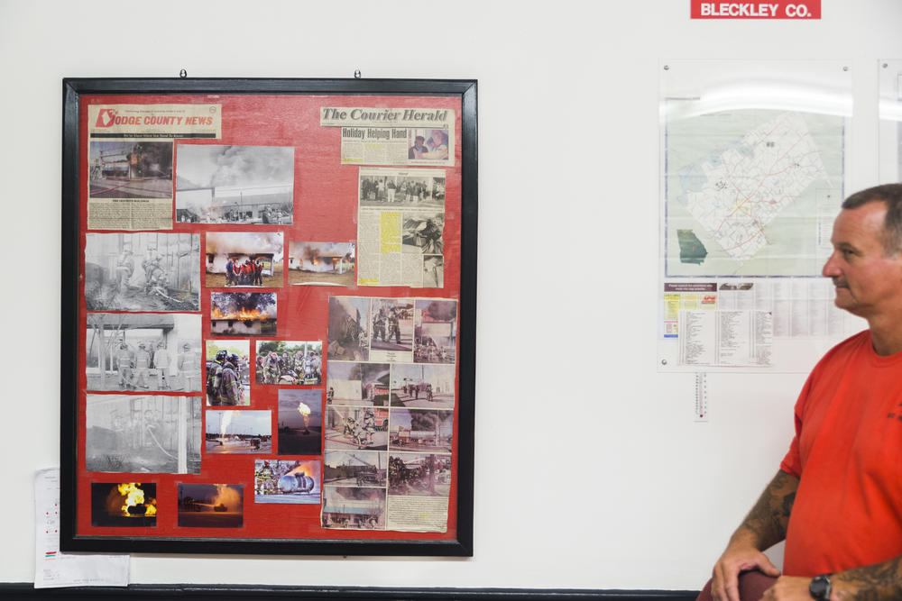 Dodge State Prison Firefighter David Foxworth with the bulletin board full of the department's news clippings, given pride of place in the fire hall.