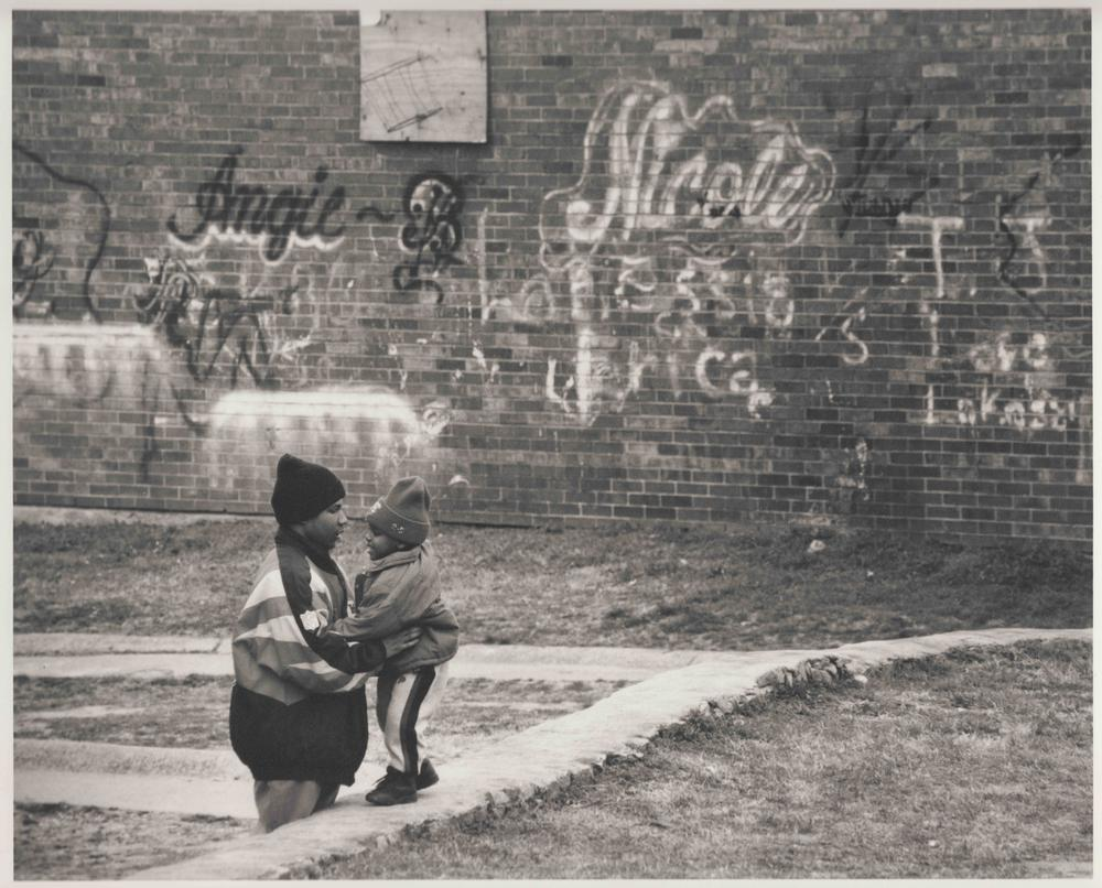 """A man and child next to a wall full of graffiti in the East Lake area of Atlanta, 1996. The documentary """"East Lake Meadows: A Public Housing Story"""" airs on PBS on Tuesday, Mar. 24 at 8 p.m."""