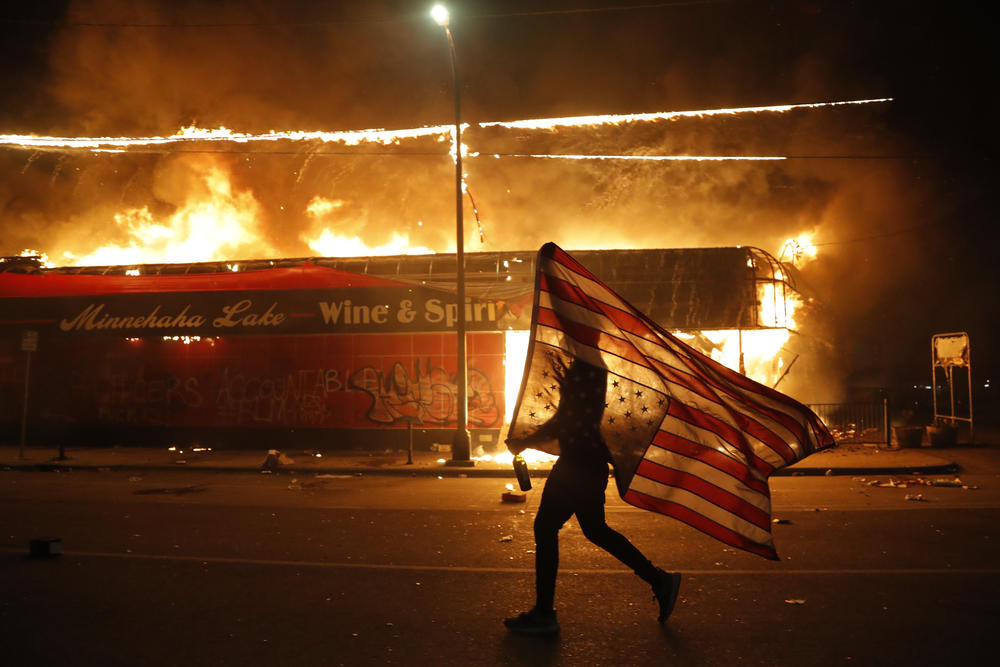 A protester carries a U.S. flag next to a burning building Thursday in Minneapolis. Protests over the death of George Floyd, a black man who died in police custody Monday occured for several days.