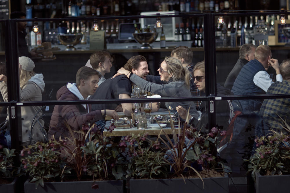 A couple hugs and laughs as they have lunch in a restaurant in Stockholm, Sweden. This photo, taken Apr. 4, 2020, illustrates Sweden's relatively relaxed response to coronavirus, in contrast with the lockdown approach taken by many other countries.