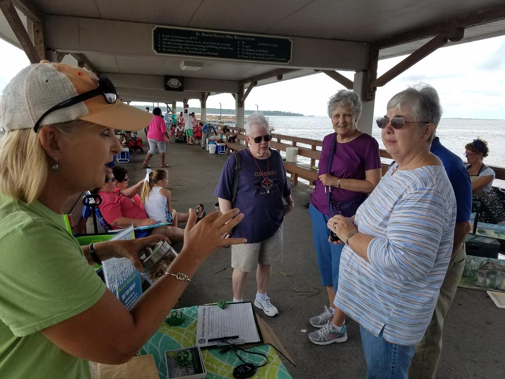 Lea King-Badyna explains to passersby why her group, Keep Golden Isles Beautiful, wants to keep cigarette butts off the beach. She's also handing out portable ashtrays.