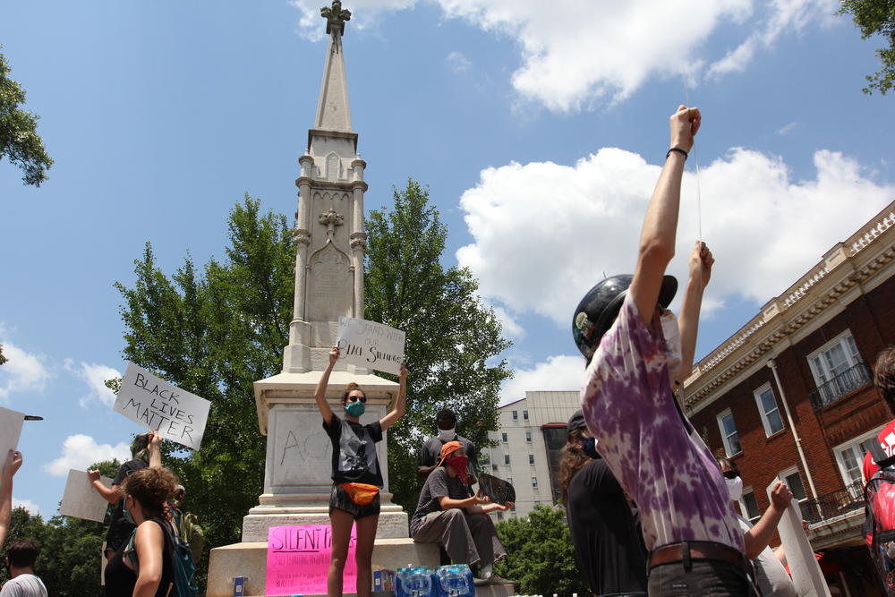 Protesters gather at a Confederate monument in Athens, which has been vandalized with anti-police slogans. The county might move the monument.