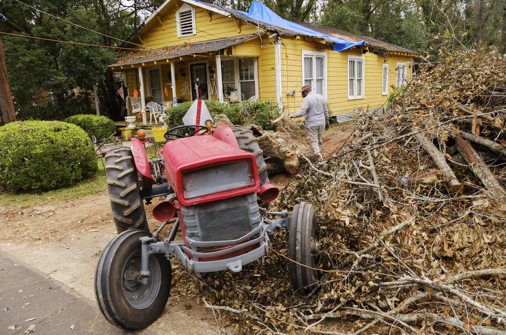 Bobby Washington his tractor to drag a piece of  oak tree downed by Hurricane Michael out of a neighbor's yard in Bainbridge in October. Decatur County was one of the hardest hit areas of the state during the storm.