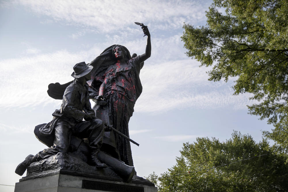 A statue depicting a Confederate soldier in Piedmont Park in Atlanta is vandalized with spray paint Monday, Aug. 14, 2017, from protesters who marched through the city last night to protest the weekend violence in Charlottesville, Virginia.
