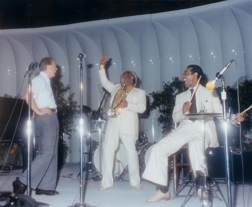 This photograph of President Jimmy Carter on stage at a White House jazz concert was taken on June 18, 1978. Carter appears in the photograph with trumpeter Dizzy Gillespie (center) and percussionist Max Roach (right).