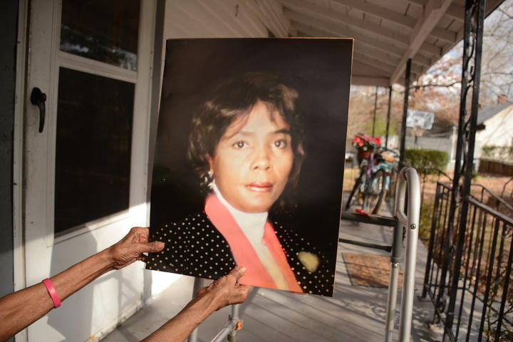 Camille McKnight showing off an old photo of herself from her front porch.