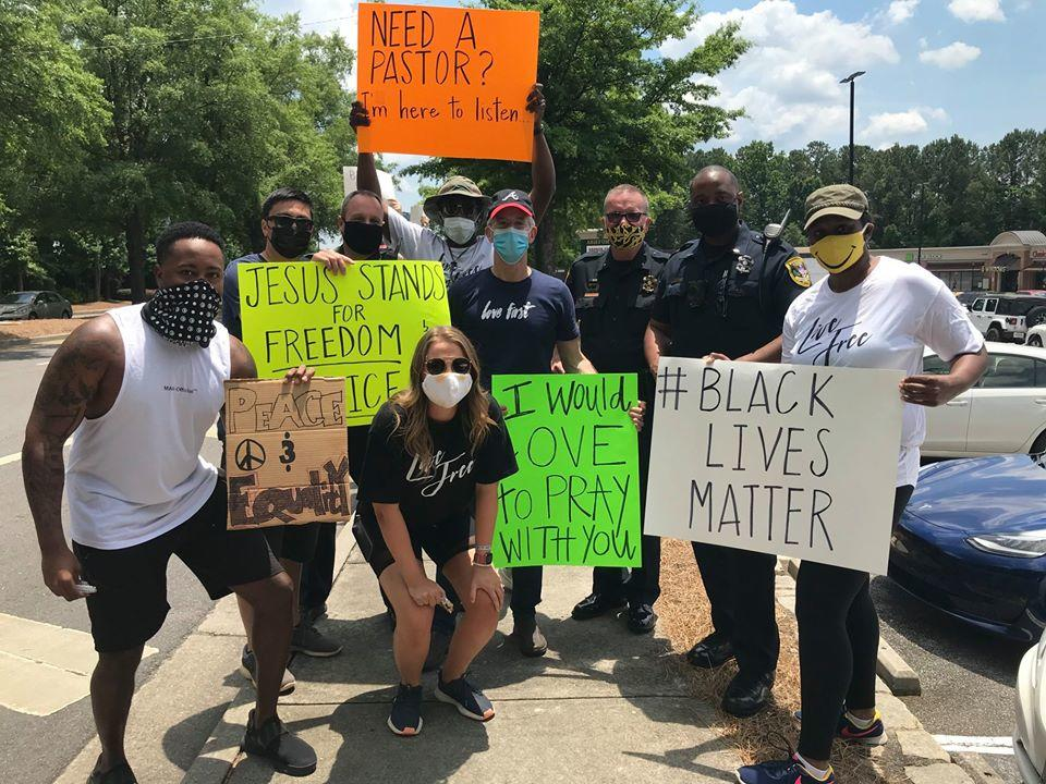 Protesters in pose for a picture with Dunwoody police officers after a protest in front of the police department's headquarters on June 1.