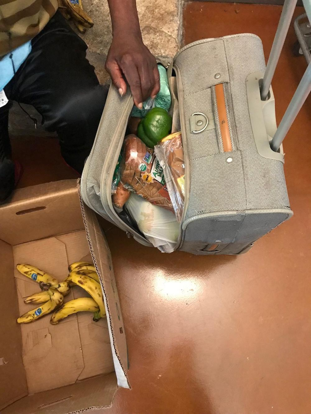 Bobby Akins stuffs his suitcase with groceries he picked at Malachi's Storehouse. He takes them to his neighbors at his apartment on Auburn Avenue.
