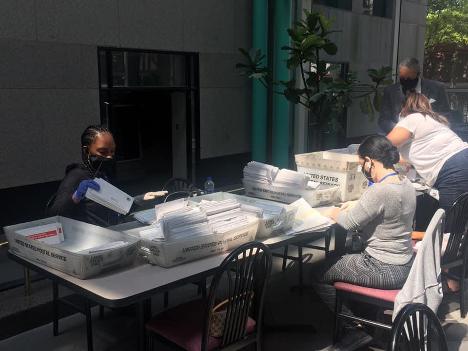Fulton County Government employees process stacks of absentee ballot applications.