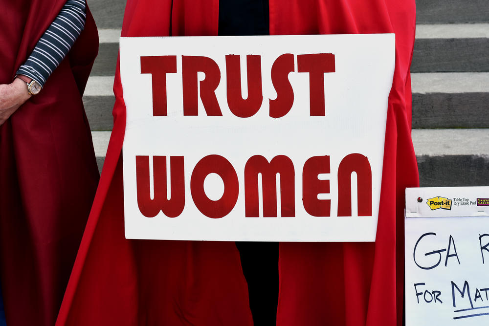 A woman holds a sign reading 'Trust Women' at a protest against Georgia's