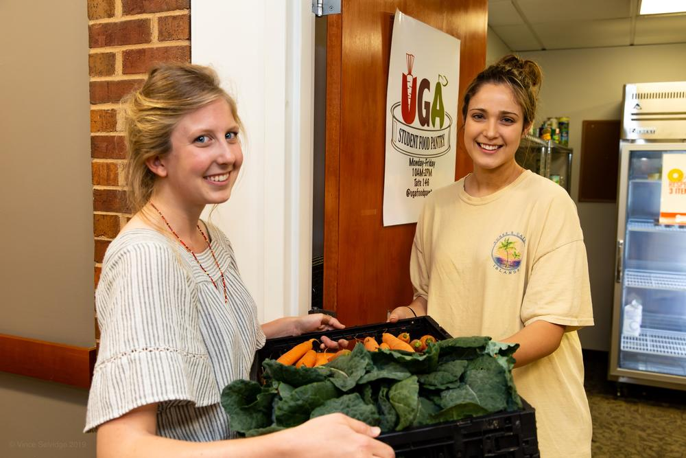 UGArden intern Lily Dabbs, a second-year geography major working toward a certificate in urban and metropolitan studies, delivers the first crop of UGArden vegetables to Ava Parisi.